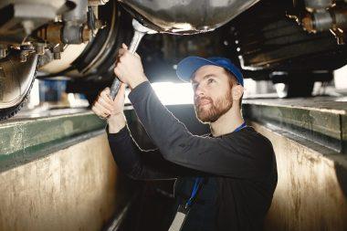 ar-mechanic-repairs-blue-car-on-rise-in-garage-6GP74X9-min
